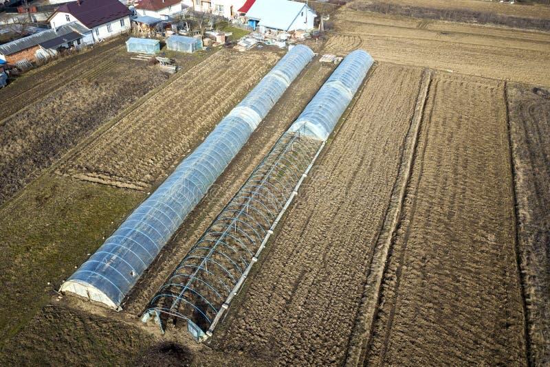 Flyg- sikt av långa välvda växthus som täckas med polyetylen i plogat vårfält åkerbruk lantbruk arkivbild