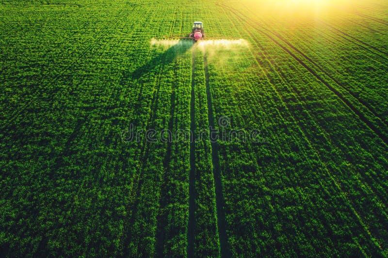 Flyg- sikt av lantbruktraktoren som plogar och besprutar på fält royaltyfri foto