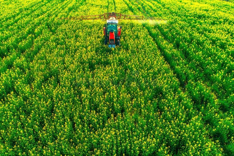 Flyg- sikt av lantbruktraktoren som plogar och besprutar på fält arkivbild
