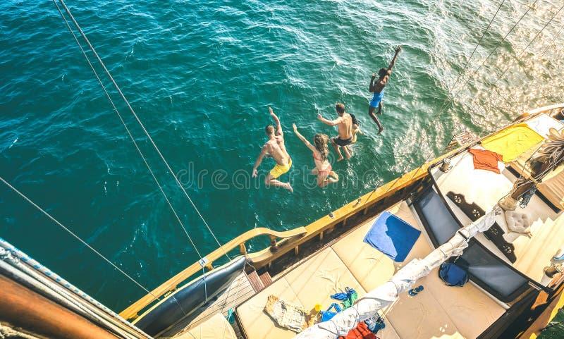 Flyg- sikt av lyckliga millenial vänner som tillsammans hoppar från segelbåten på havshavtur - rika grabbar och flickor som har g royaltyfri foto