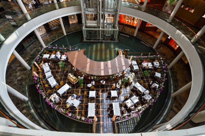 Flyg- sikt av matställear som tycker om ett mål på en restaurang på shoppesna på Marina Bay Sands arkivfoto