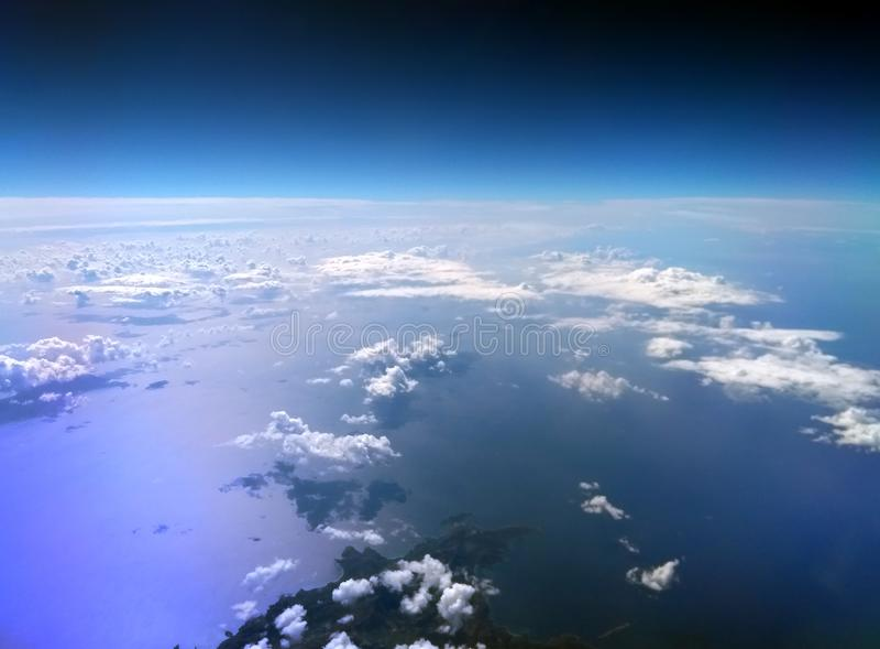 Flyg- sikt av medelhavet som tas från ett flygplan med mörker - blå himmel och moln reflekterade på vattnet och en ö royaltyfri foto