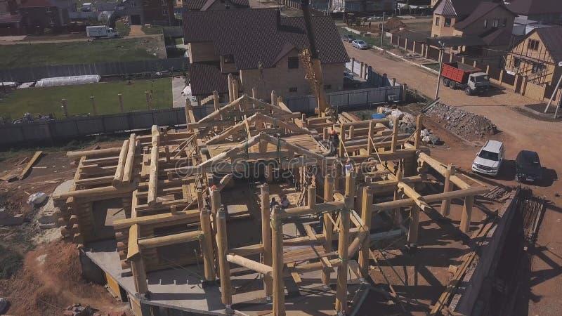 Flyg- sikt av ny träpågående stugakonstruktion, arbetare på överkanten av träkolonner och konstruktion royaltyfria bilder