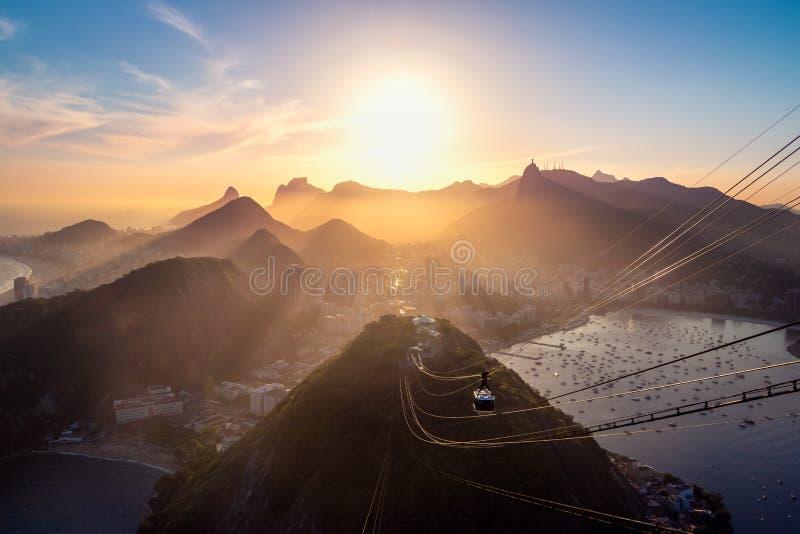 Flyg- sikt av Rio de Janeiro på solnedgången med det Urca och Corcovado berget och den Guanabara fjärden - Rio de Janeiro, Brasil arkivfoto