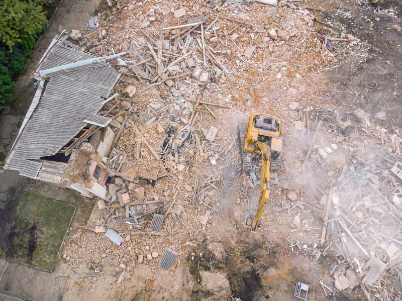 Flyg- sikt av rivningplatsen med förstörd gammal byggnad och den gula grävskopan royaltyfri foto