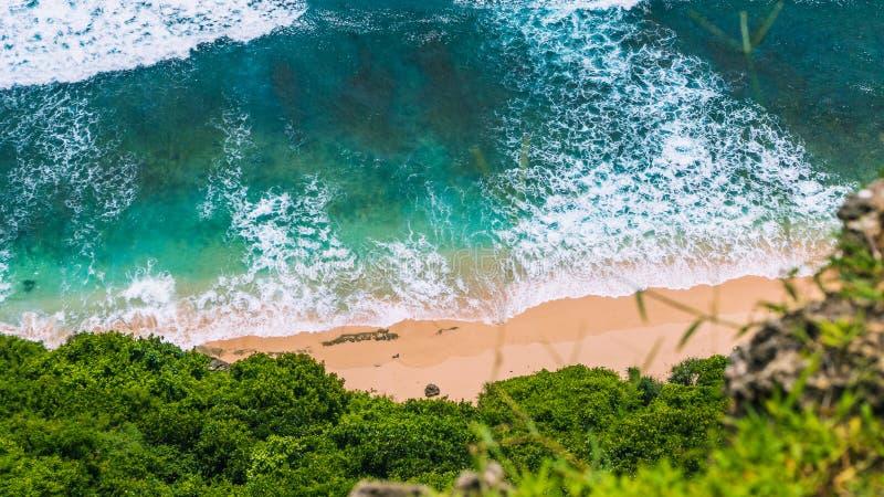 Flyg- sikt av rullande turkoshavvågor över den rena klara sandiga stranden på solig dag Omgivet av den frodiga gröna djungeln arkivfoto