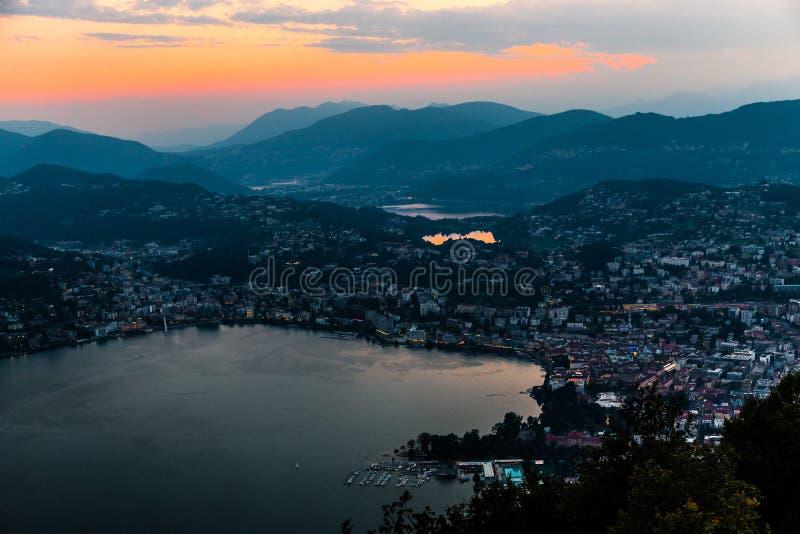Flyg- sikt av sjön Lugano som omges av berg och aftonstaden Lugano på under den dramatiska solnedgången, Schweiz, fjällängar royaltyfria foton