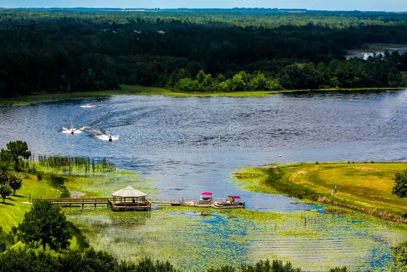 Flyg- sikt av sjön med Jet Ski ryttare, skeppsdockor och pontonfartyg royaltyfri foto