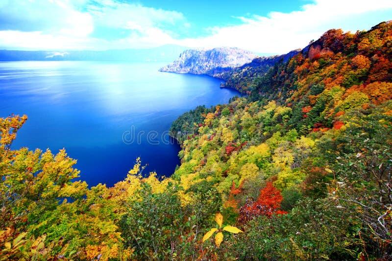 Flyg- sikt av sjön Towada med färgrik höstlövverk royaltyfria bilder