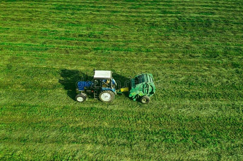 Flyg- sikt av skördfältet med den flyttande höbalen för traktor arkivfoto