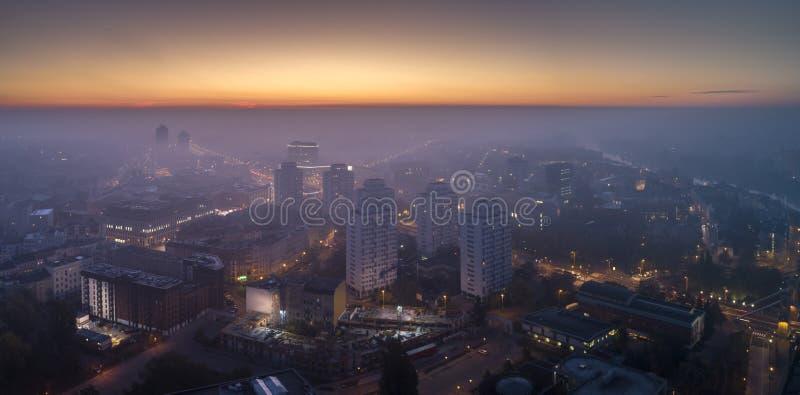 Flyg- sikt av smogen över den vakna staden på gryning, byggnader som täckas med dimma, och smog royaltyfri foto