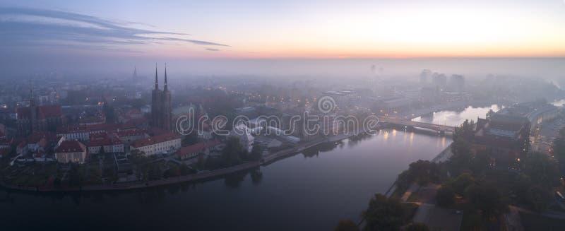 Flyg- sikt av smogen över den vakna staden på gryning, i avståndsbyggnaderna som täckas med dimma och smog royaltyfri fotografi