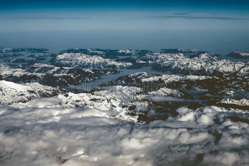 Flyg- sikt av snöig berg i vinter Flyg på solnedgången ovanför molnen arkivfoton