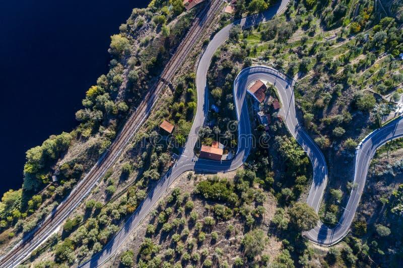 Flyg- sikt av spår för en slingrig väg och drevlängs Taguset River nära byn av Belver i Portugal arkivbilder