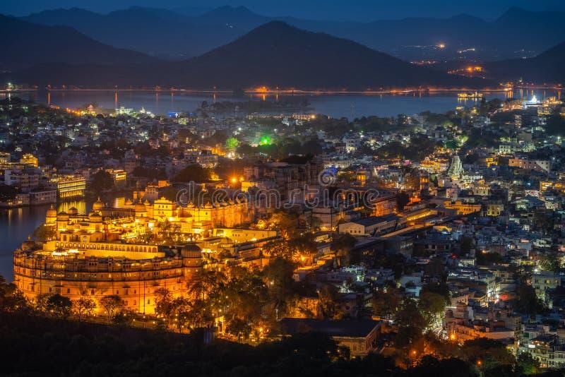 Flyg- sikt av stadsslotten efter solnedgång Udaipur Indien arkivfoto