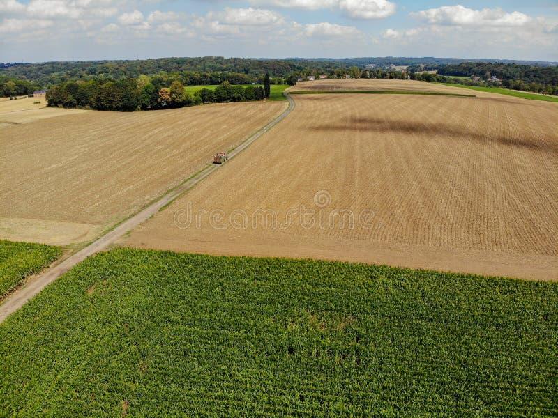 Flyg- sikt av traktoren på vägen bredvid åkerbrukt fält arkivbild