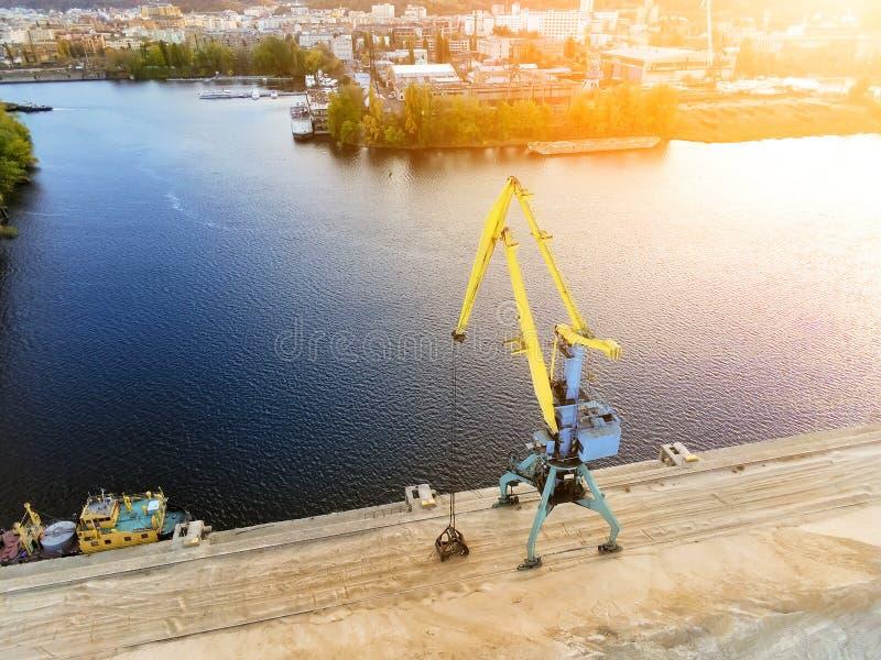 Flyg- sikt av tung kranpäfyllningsvaror i storförpackning på terminalen för port för Dnieper flodlast i Kiev på aftonsolnedgångti royaltyfria bilder
