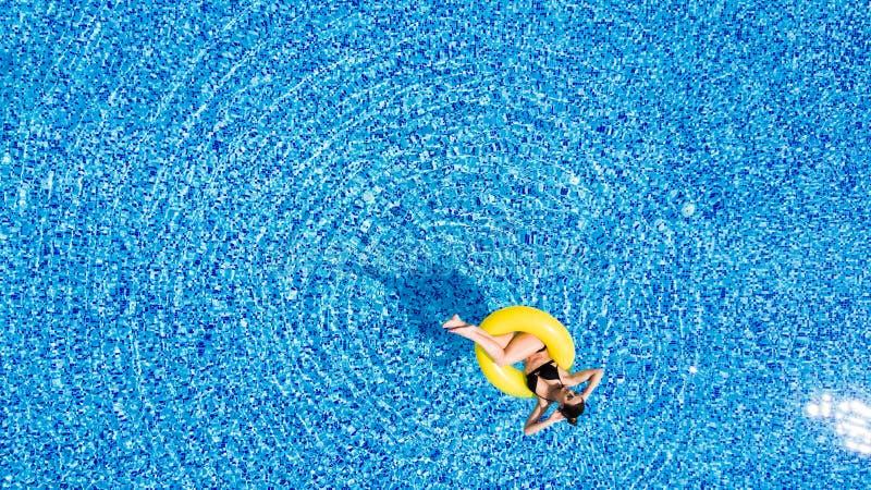 Flyg- sikt av ung brunettkvinnasimning på den uppblåsbara stora gula cirkeln i pöl royaltyfri bild