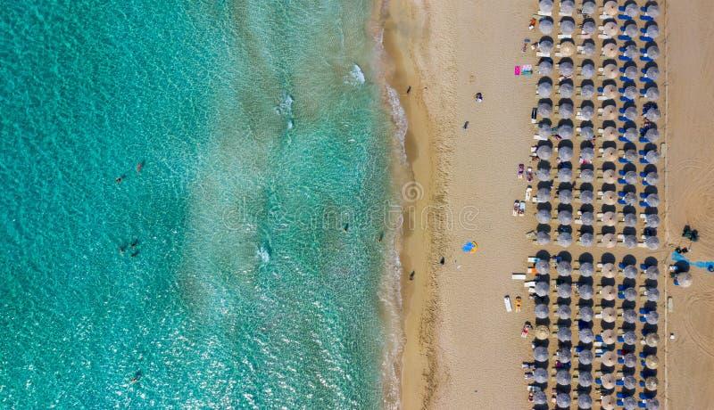 Flyg- sikt av uppe på ner den flyg- sikten av att förbluffa stranden med paraplyer och turkoshavet på solnedgången Medelhav Kreta arkivfoto