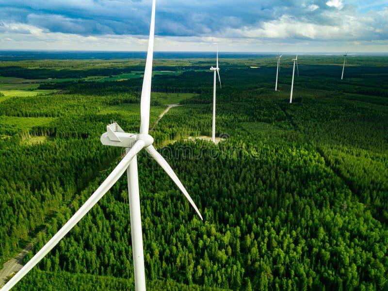 Flyg- sikt av väderkvarnar i sommarskog i Finland Vindturbiner för elkraft med rent och förnybara energikällor royaltyfria foton