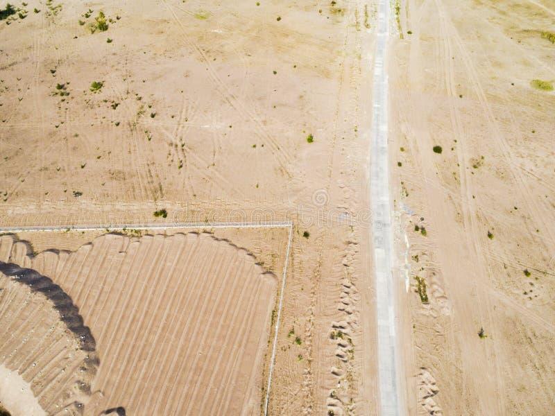 Flyg- sikt av vägen med bilen Flyg- sikt av en landsväg med sand Förbigå för bil Flyg- konstruktionsväg Flyin för flyg- sikt royaltyfria foton