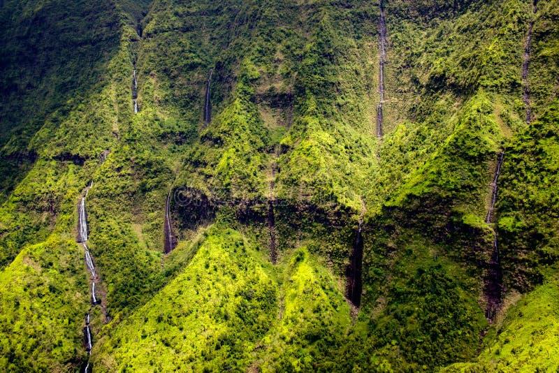 Flyg- sikt av vattenströmmar, vattenfall och det frodiga landskapet, Kauai royaltyfri fotografi