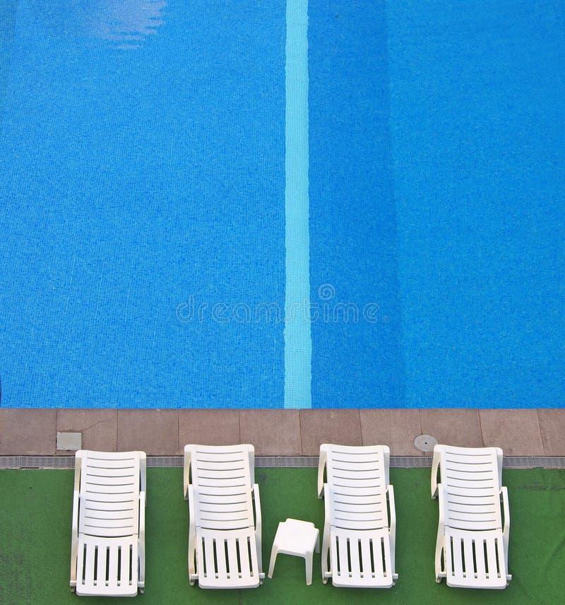 Flyg- sikt av vita sunbeds på sidan av en blå simbassäng med ljust vatten och ett band i tegelplattorna fotografering för bildbyråer