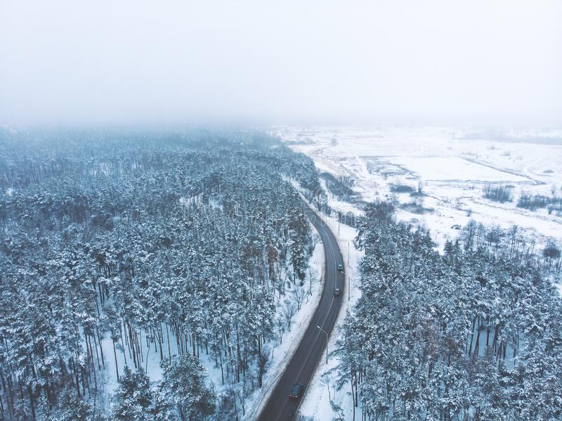 Flyg- sikt för fågelöga av den lantliga asfaltvägen i härligt vinterlandskap med skogen i insnöad dimmig dag royaltyfri fotografi