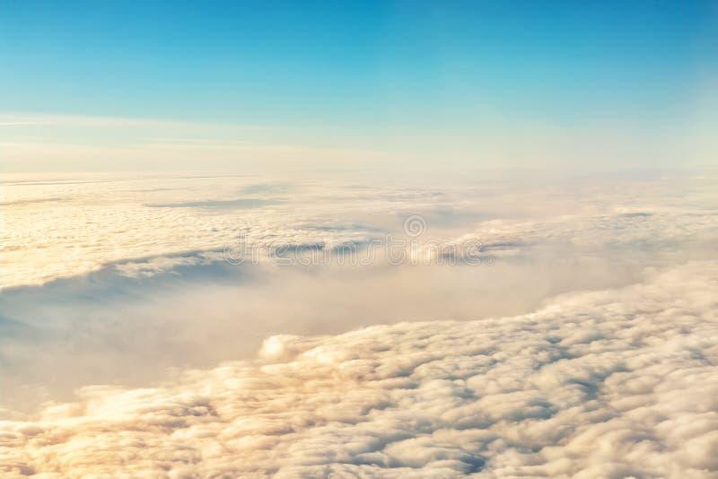 Flyg- sikt för härlig scenisk dramatisk morgonsoluppgångcloudscape från plant fönster Lutningen färgade fluffiga moln under flygp arkivbild