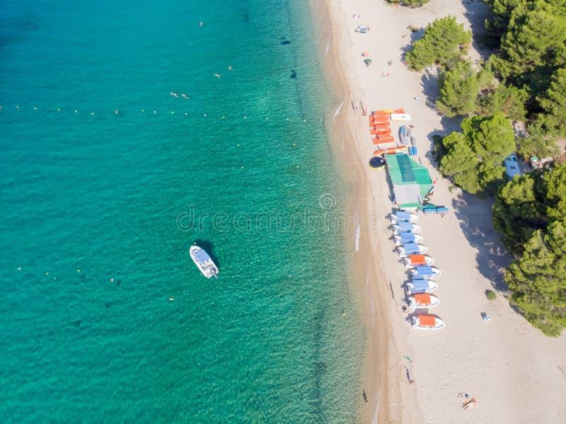 Flyg- sikt för surr av havskusten, den sandiga stranden och blått vatten Fartyg nära stranden med lotten av parasoller arkivfoton