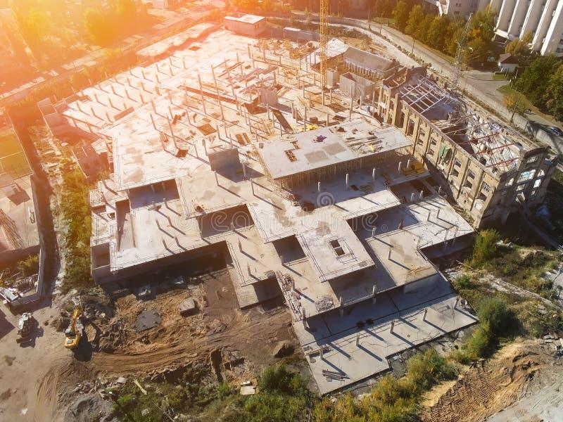 Flyg- sikt f?r konstruktionsplats Galleriabyggnadsgrund med fasta konkreta pelare Tungt maskineri och kran f arkivbild