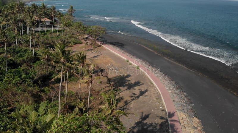 flyg- sikt 4K av den svarta sandstranden på öst av den tropiska Bali ön, Indonesien royaltyfri bild