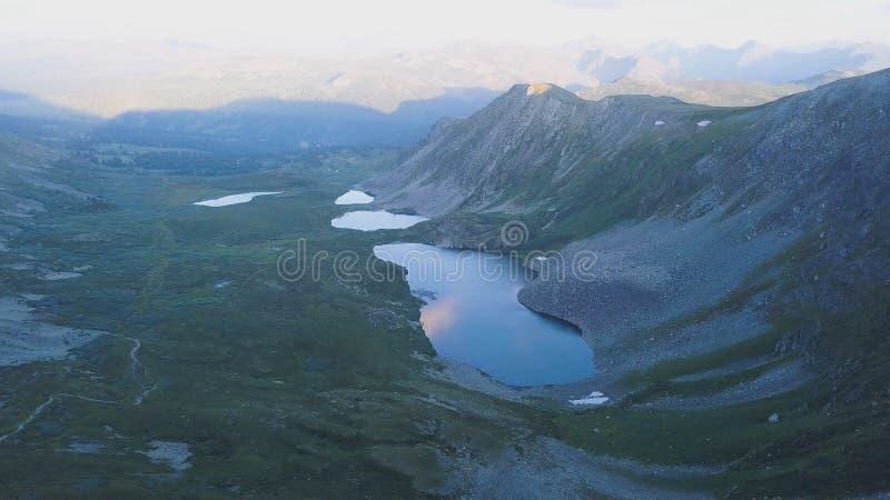 Flyg- sikt på bergmaximum med sjöbakgrund Fantastiskt berglandskap med damm royaltyfri fotografi