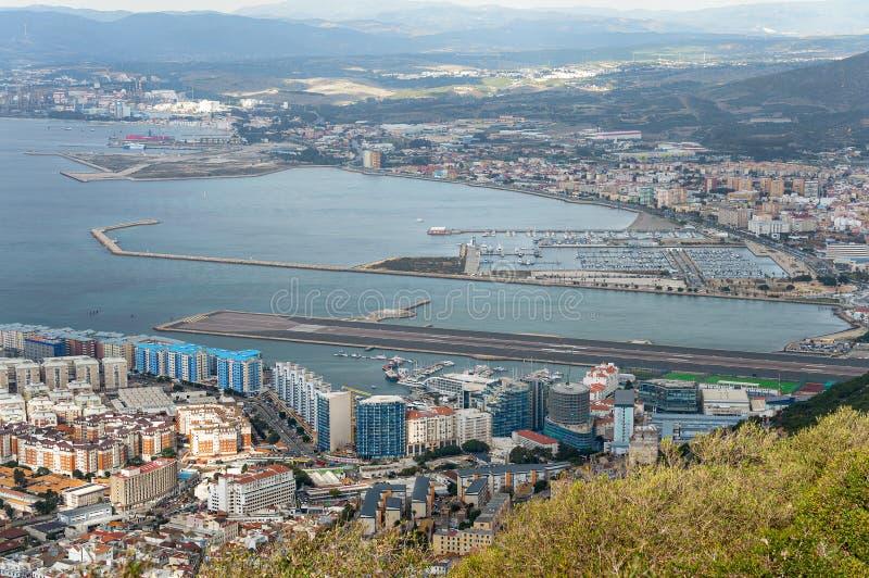 Flyg- sikt på stads- och flygplatslandningsbana av Gibraltar och den spanska LaLinea staden på en bakgrund royaltyfri foto