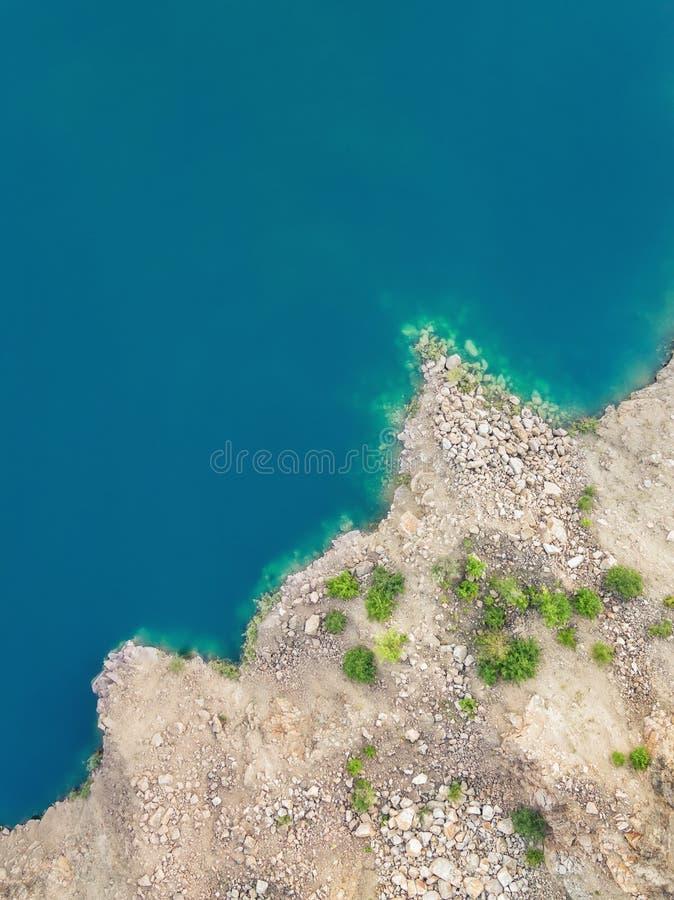 Flyg- sikt på stenig kust och blått rent vatten av sjön royaltyfri foto