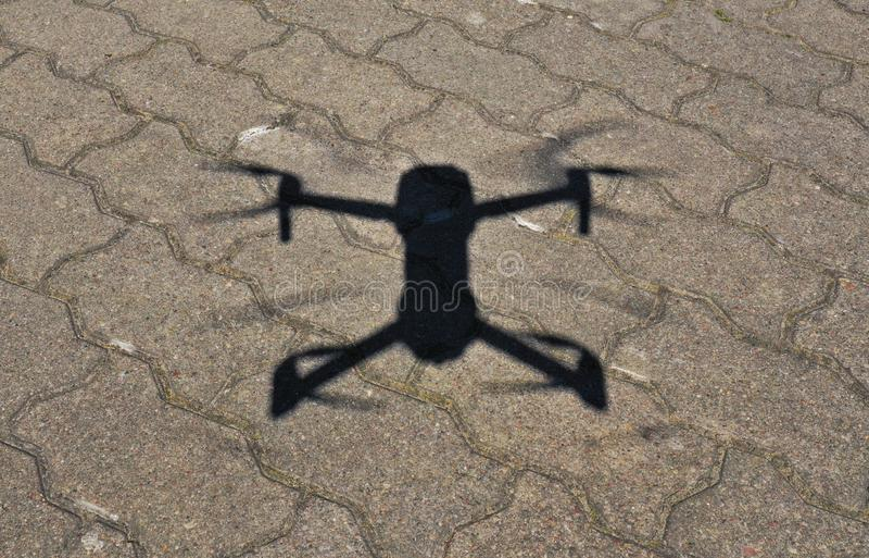 Flyg- sikt på surrskugga på konkret jordning, Quadcopter under landningtillvägagångssätt i solig dag royaltyfri bild