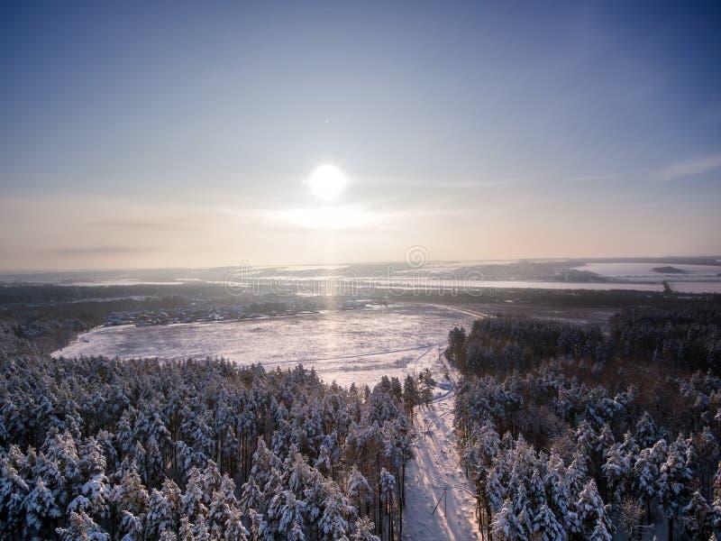 Flyg- sikt på vinterskog och fält Solig dag i snöfall, snöflingor på sunlights Sjö och flod på bakgrund arkivfoto