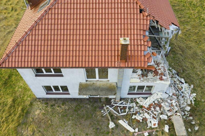 Flyg- sikt p? det skadade r?da enkla hustaket efter stark vind eller explosion H?l i taket och golvet Spillror p? jordningen arkivbilder