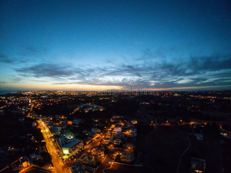 Flyg- sikt p? staden p? natten, Albufeira, Portugal Upplysta gator p? solnedg?ngen royaltyfria foton