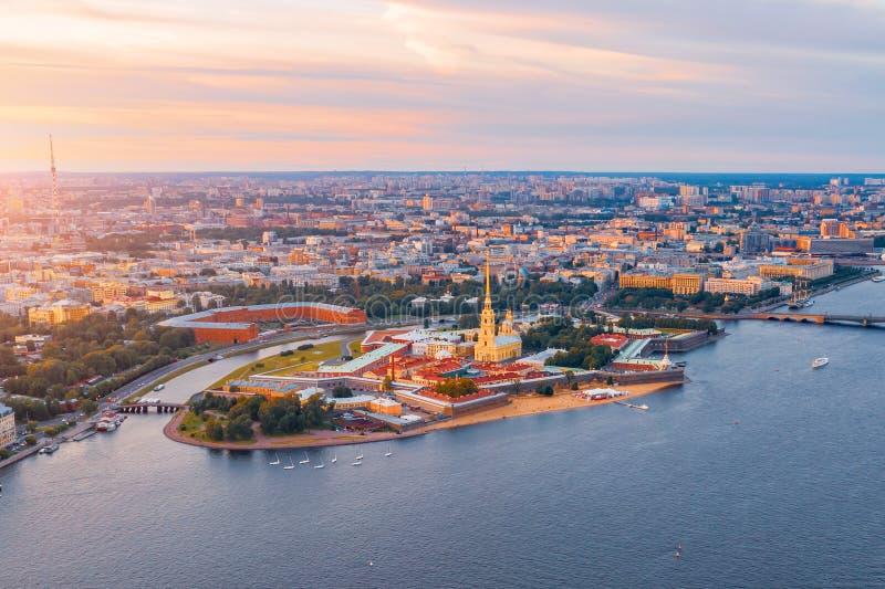 Flyg- sikt som är panorama- av den Peter och Paul domkyrkan på den röda solnedgången, väggar av fästningen, i St Petersburg royaltyfri foto