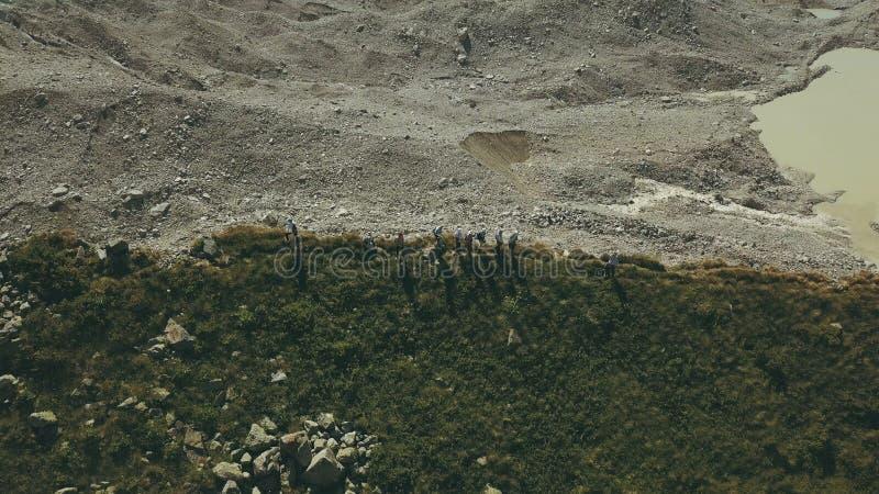 Flyg- sikt som fotvandrar gruppanseende på bergkanten Klättra ett berg arkivbilder