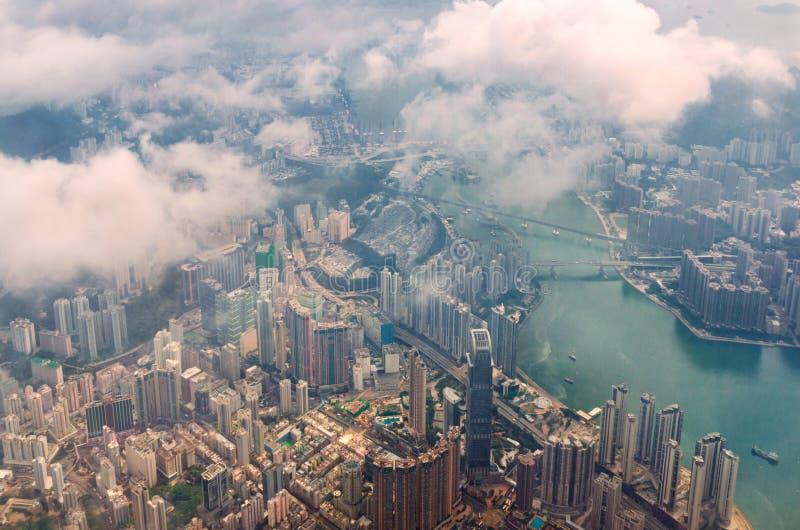 Flyg- sikt till och med molnen till en stor metropolisstad av Hong Kong royaltyfri foto