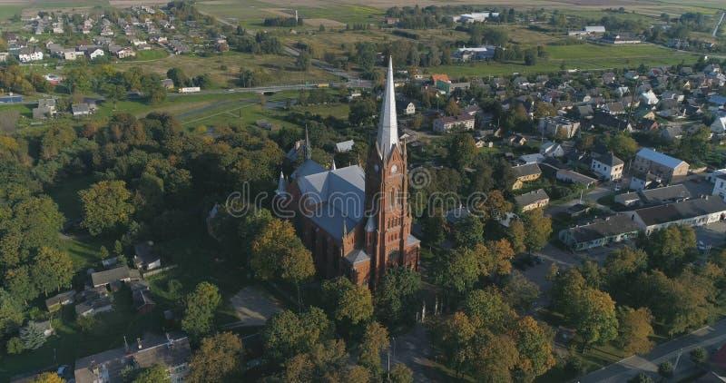 Flyg- skott av den St John kyrkan av Ramygala i Litauen Panorama av staden i tidig höst royaltyfri foto