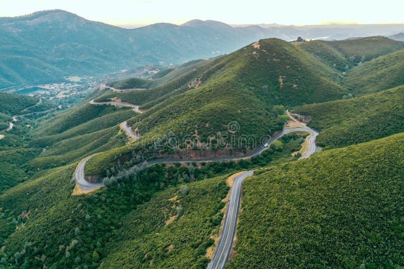 Flyg- skott av härliga gröna kullar och berg med en smal curvy väg i mitt royaltyfri foto