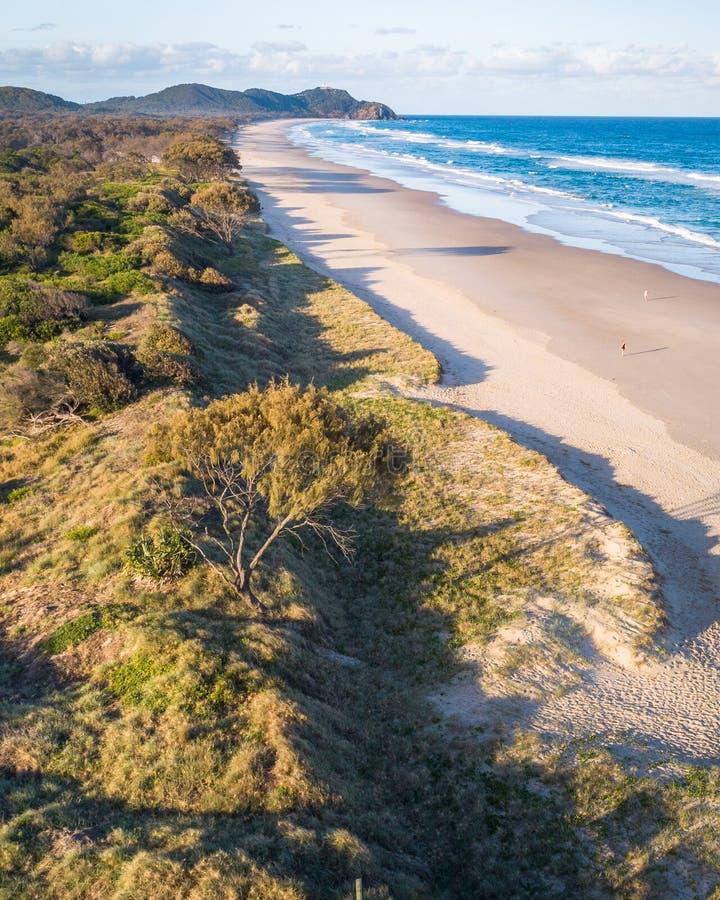 Flyg- skott på soluppgång över havet, sandstranden med simmare och surfare som tycker om sommar Byron Bay talgstrand royaltyfria foton