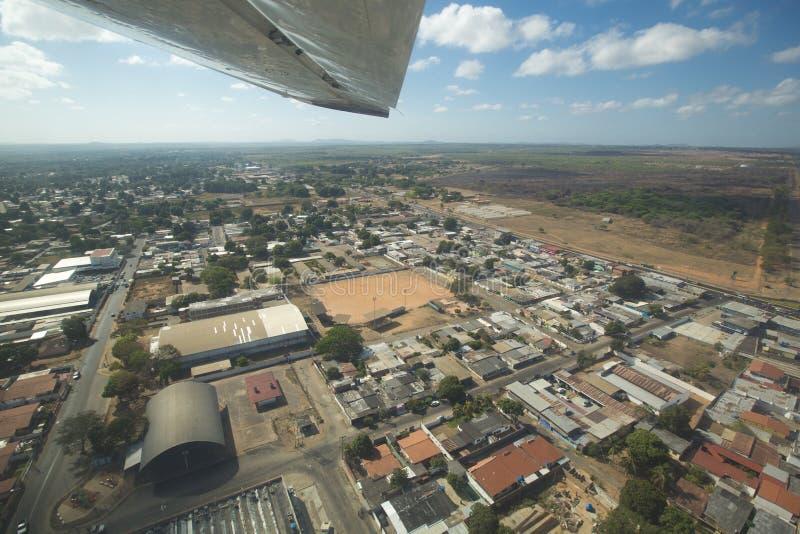 Flyg- solig sikt av Ciudad Bolivar med skogen, moln och fotografering för bildbyråer
