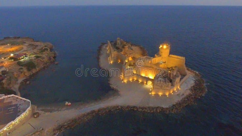Flyg- solnedgångsikt av Fortezza Aragonese, Calabria, Italien royaltyfria foton