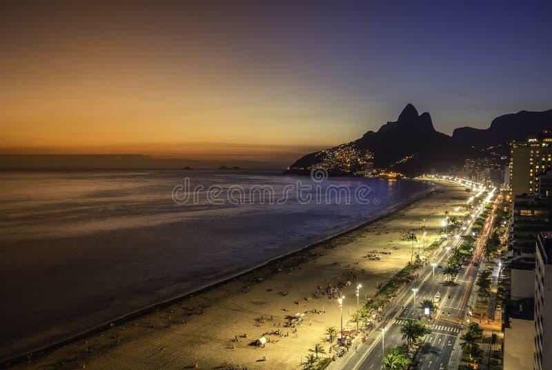 Flyg- solnedgångsikt med ljusa läckor på den Ipanema stranden i Rio de Janeiro royaltyfria bilder