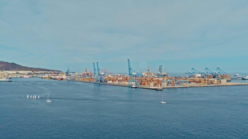 flyg- surrbild av hamnen med talrika behållare som travas upp bredvid kranans ett litet segla jollelopp arkivbild