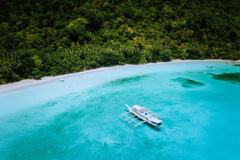 Flyg- surrsikt av en vidsträckt scenisk tropisk sandig strand med frodiga rainforest- och bancafartyg Rått drömlikt ställe för fl arkivfoton